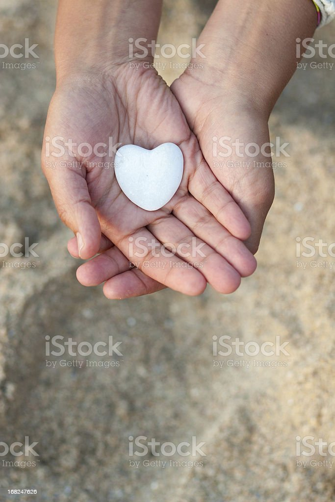 Hands holding a heart on defocused sand background. royalty-free stock photo