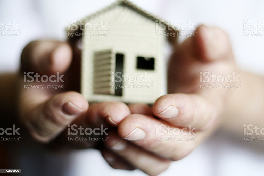 Hands holding a model of a house indicating real estate  stock photo