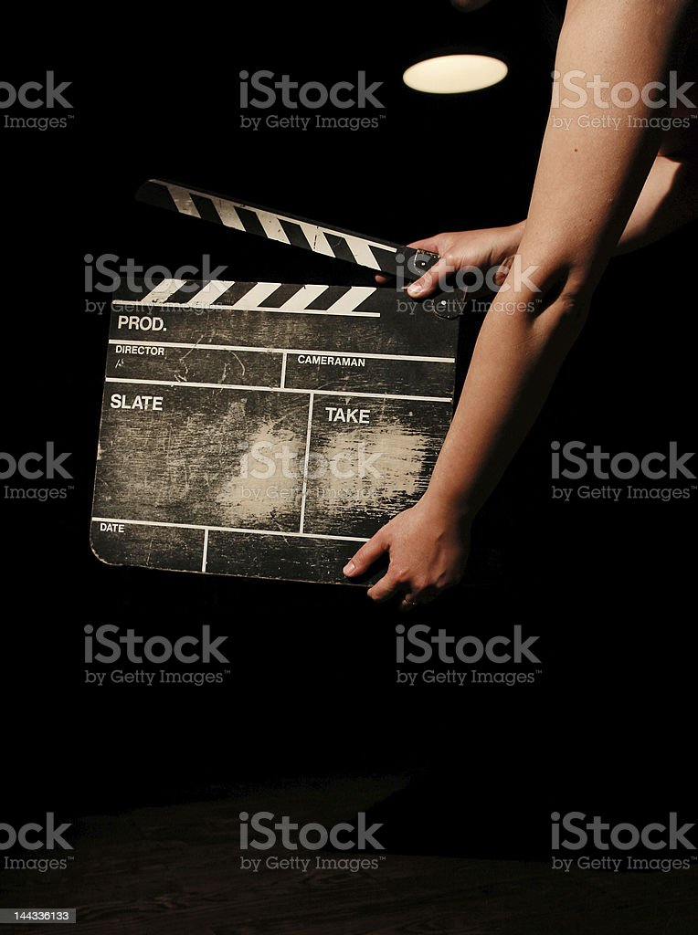 Hands holding a movie clapper board on black background stock photo