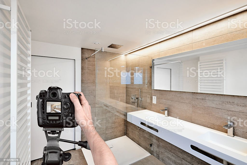 Hands holding a professional camera on tripod taking picture stock photo