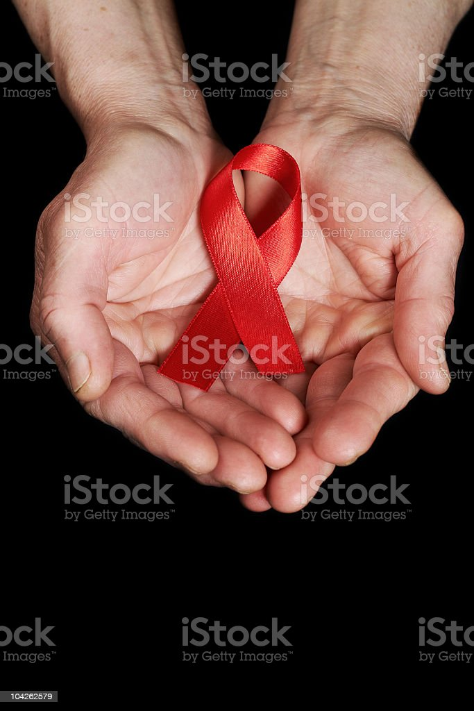 Hands holding a red AIDS awareness ribbon stock photo
