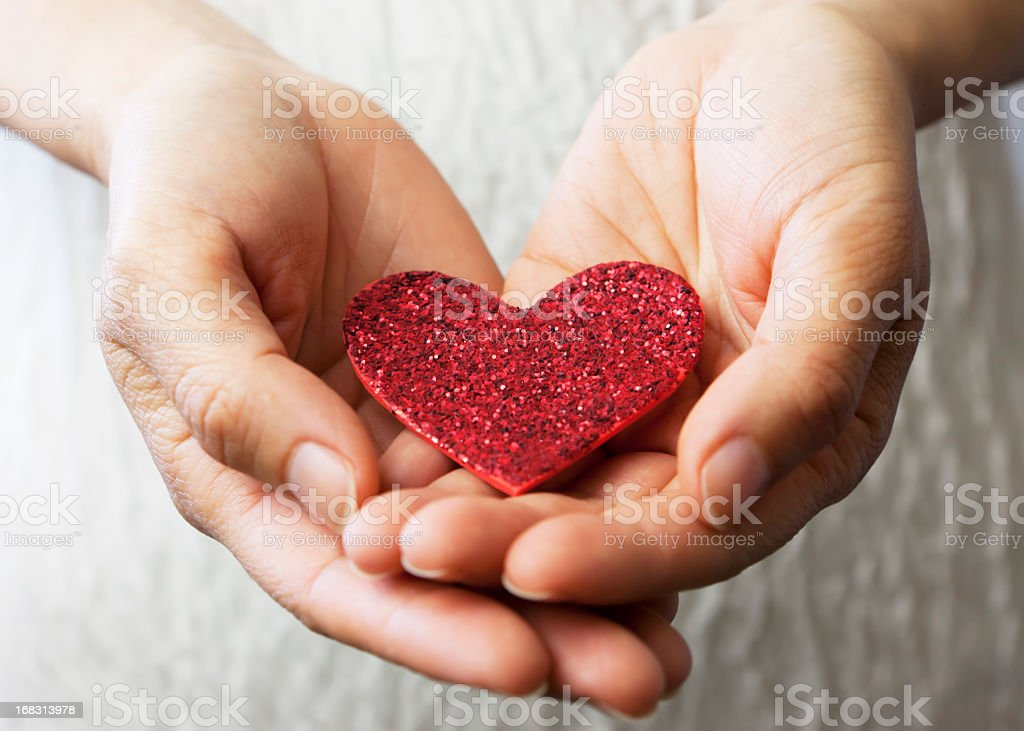Hands holding a red heart. stock photo