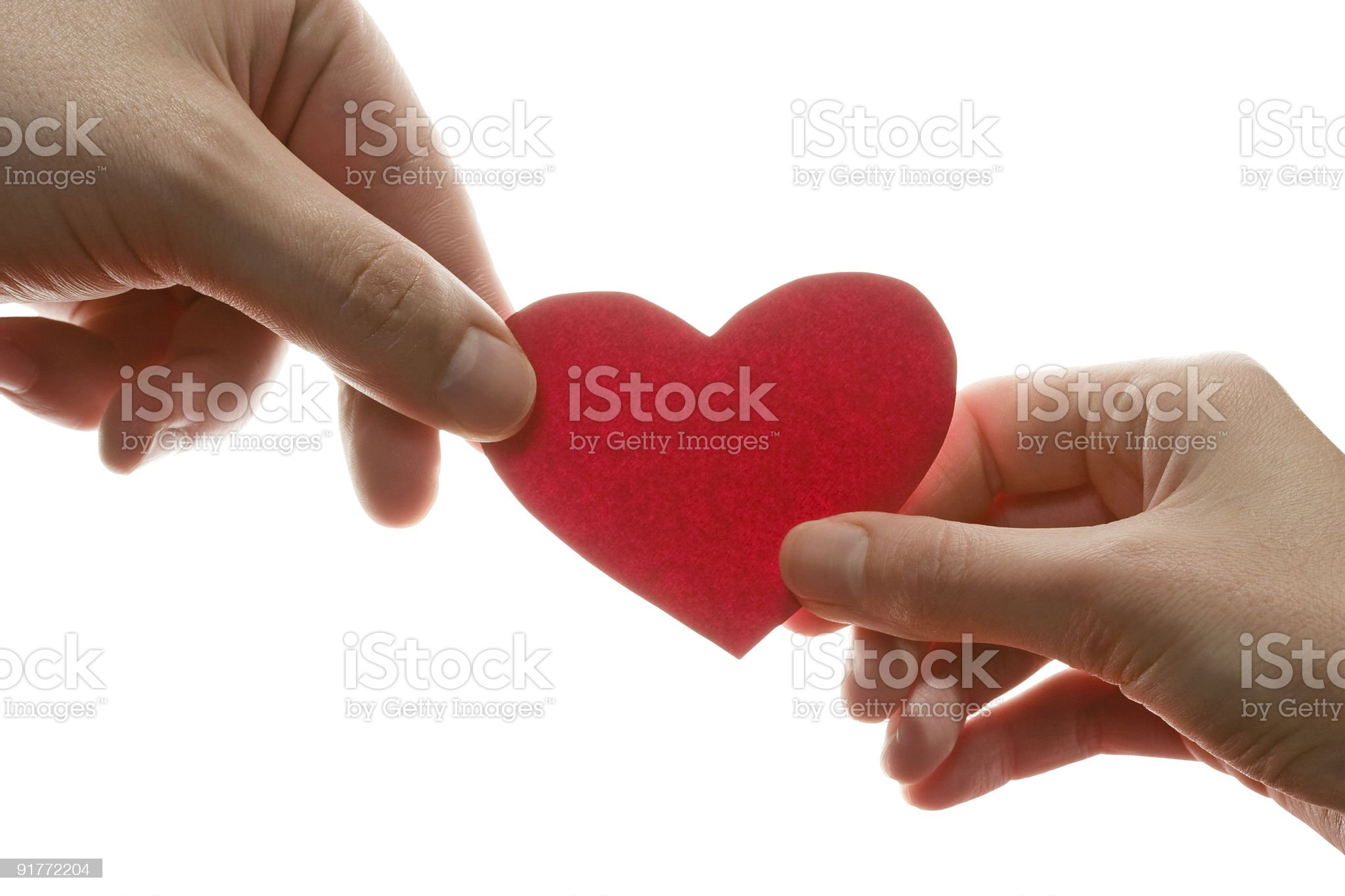 2 hands holding a red piece of paper shaped like a heart royalty-free stock photo