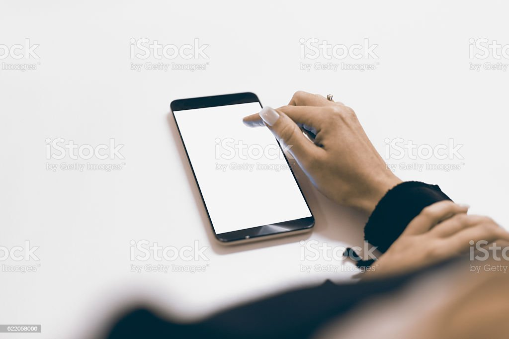 Hands holding a smart phone with a blank, white screen. stock photo