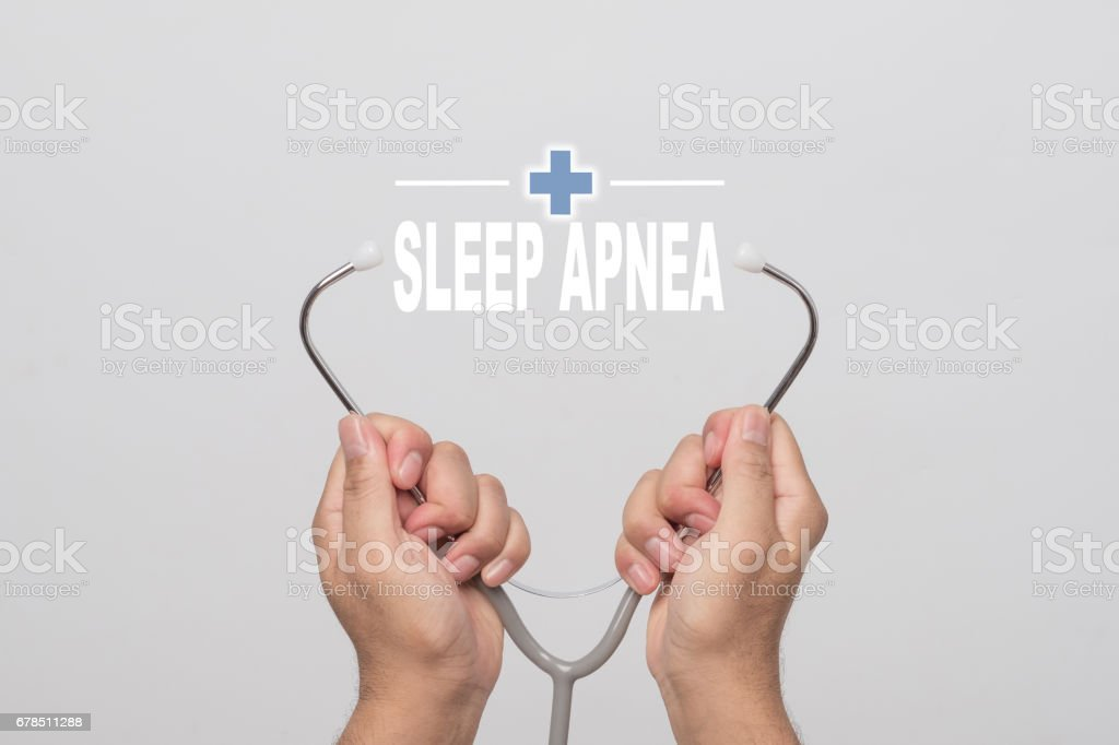 Hands holding a stethoscope and word  'SLEEP APNEA' on gray background. concept Healthy. stock photo