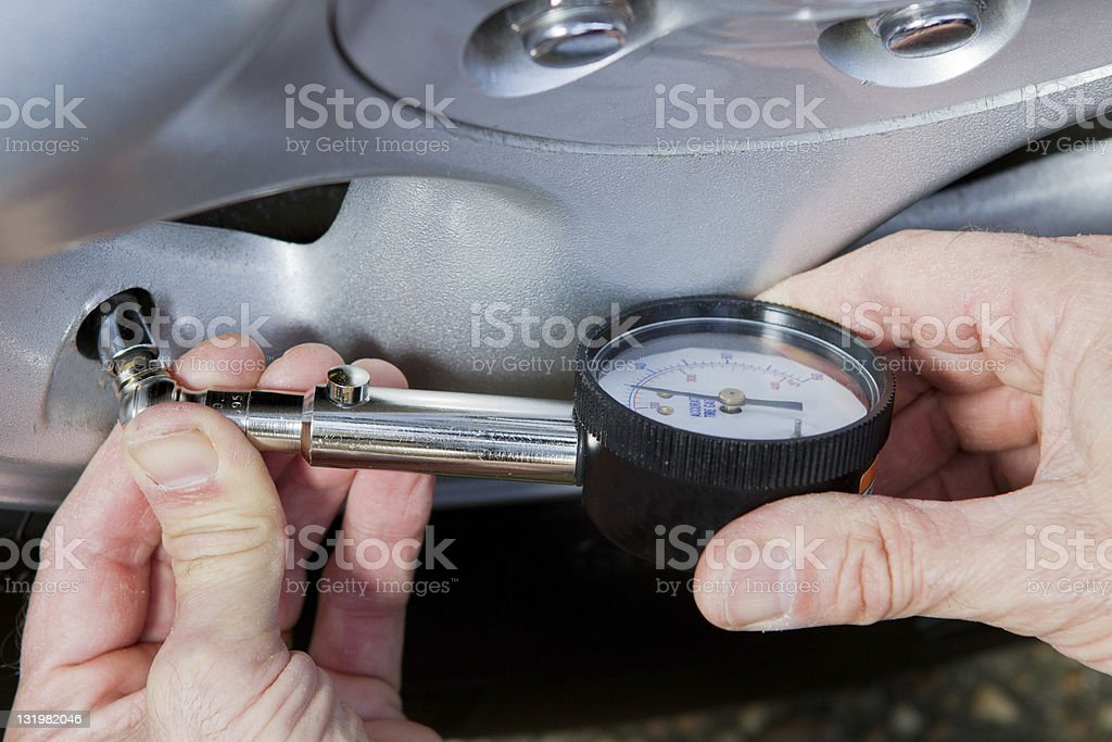 Hands holding a tire guage on a wheel valve stem. stock photo
