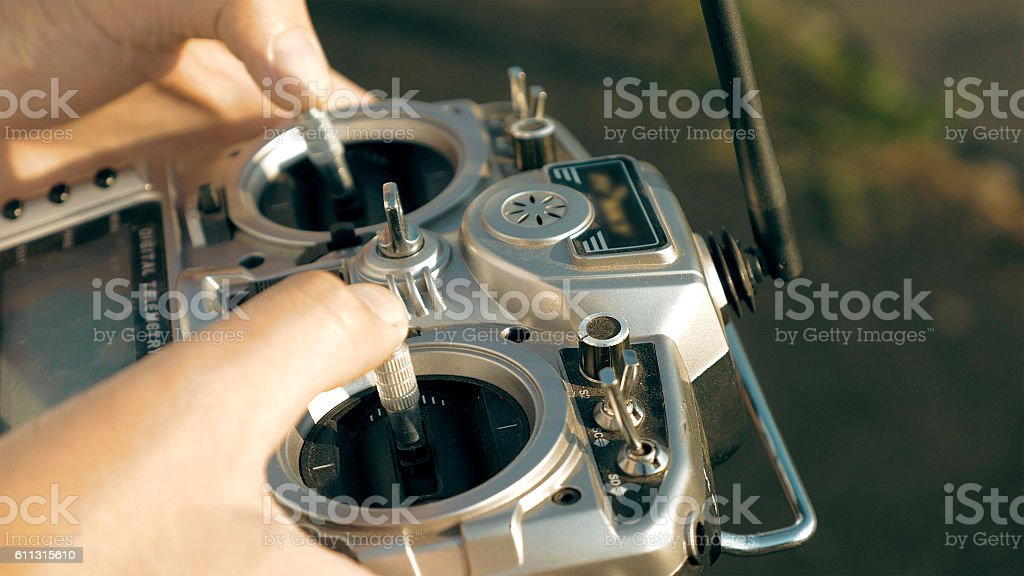 Hands holding a transmitter controlling FPV drone stock photo