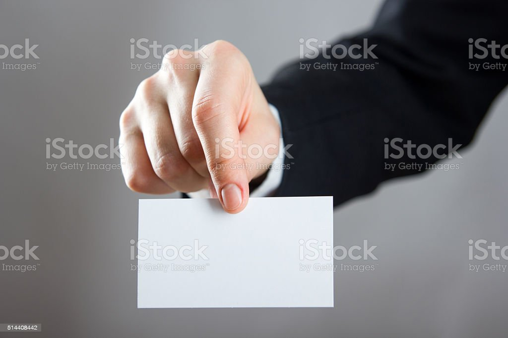 Hands holding a white business visit card, gift, ticket, pass stock photo
