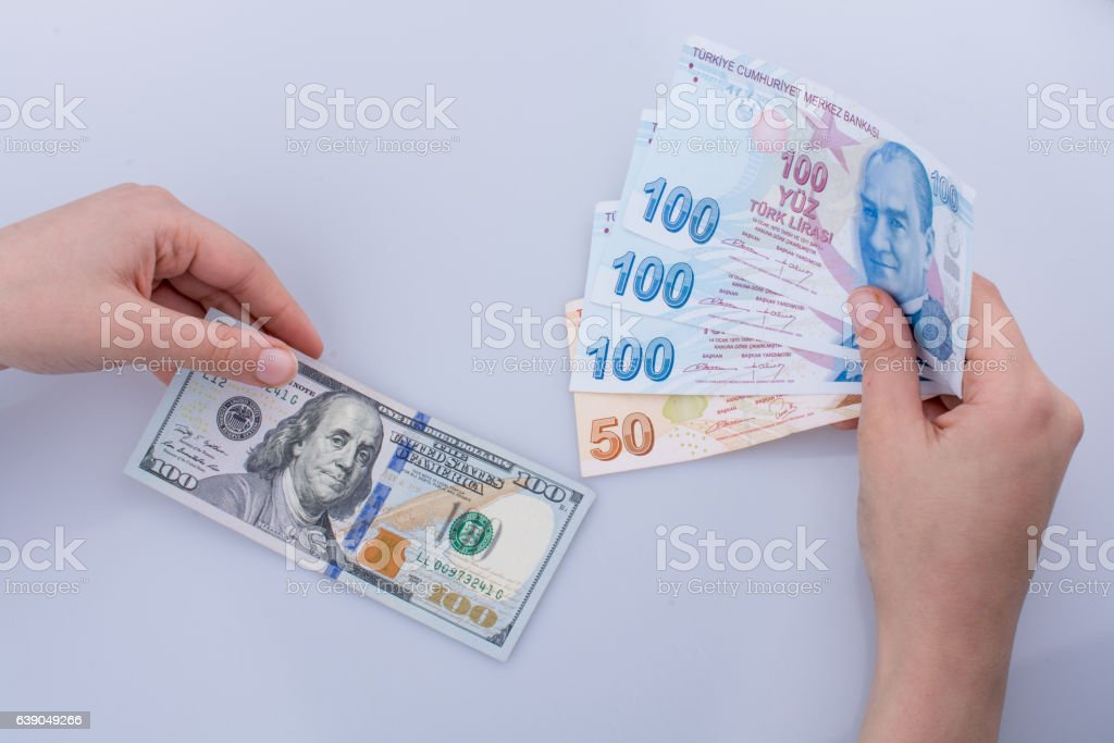 Hands holding American dollar banknotes and Turksh Lira banknote stock photo