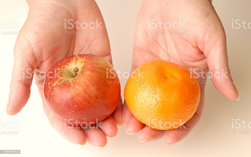 Hands holding an apple and an orange stock photo