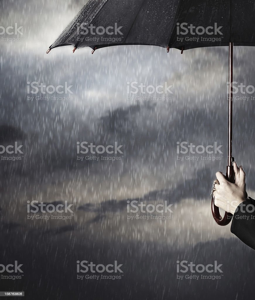 Hands holding an umbrella in the rain stock photo