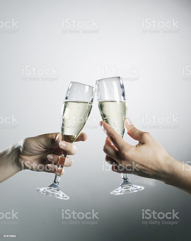 Hands holding and toasting champagne flutes stock photo