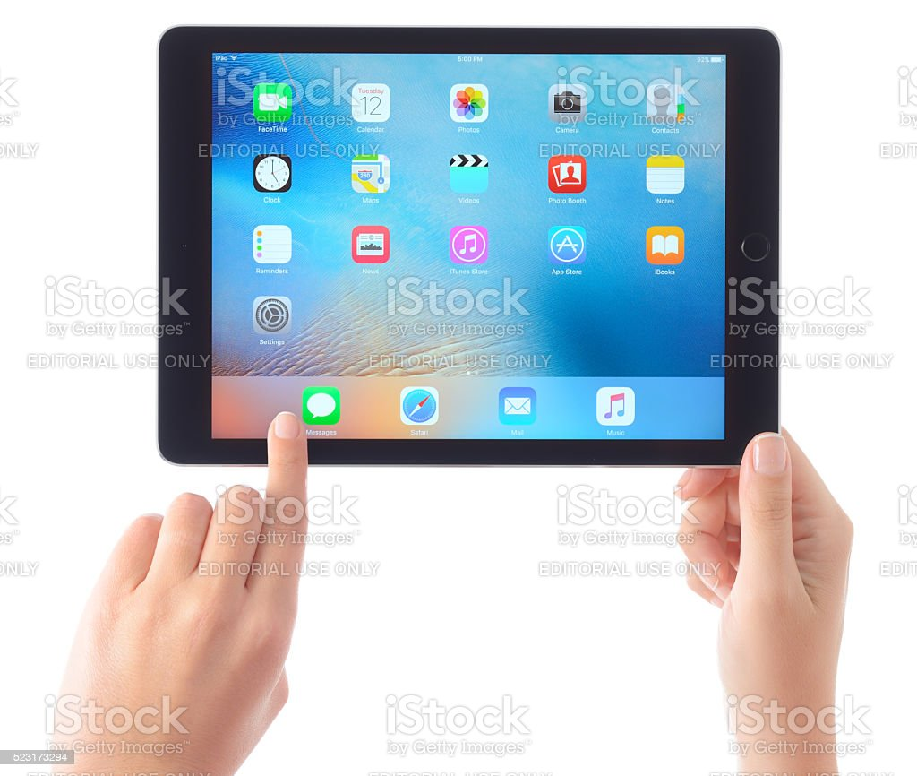 Hands holding Apple iPad Air on white stock photo
