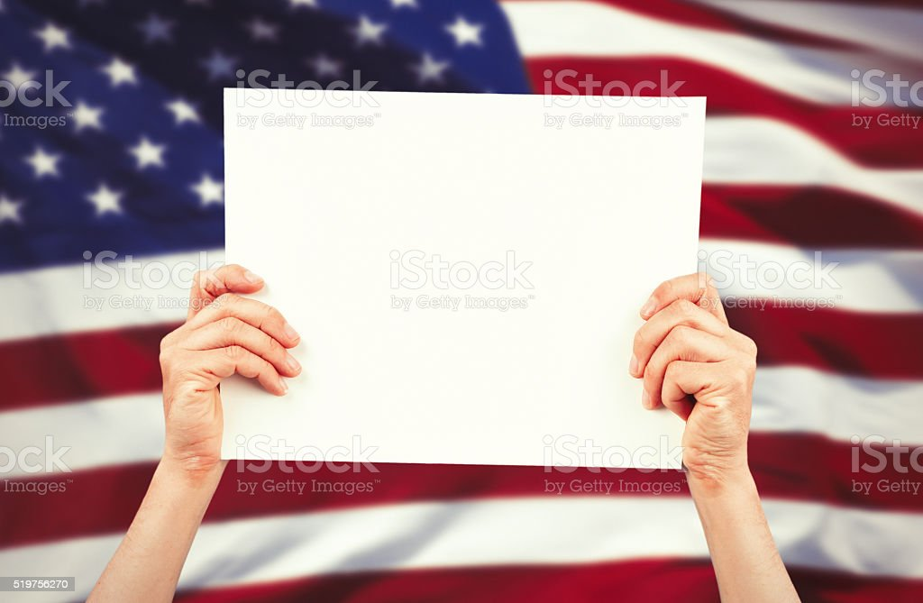 Hands holding blank banner with us flag behind stock photo