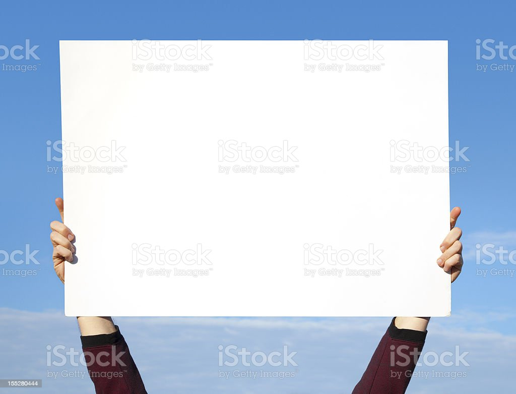 Hands Holding Blank White Sign in Sky stock photo