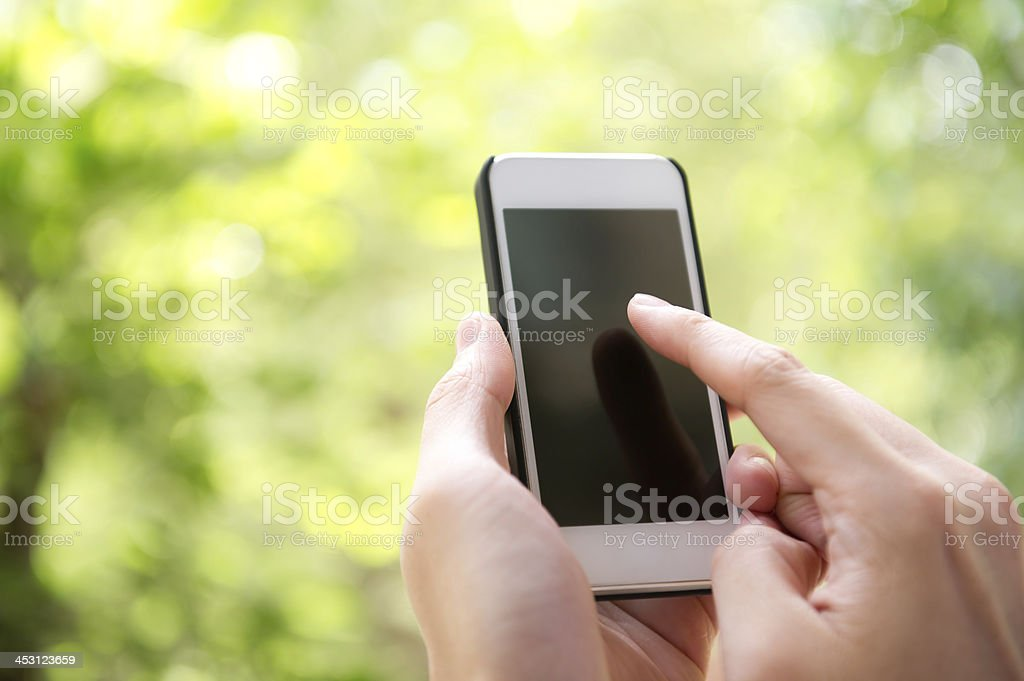 Hands holding blank white smart phone against green backdrop royalty-free stock photo