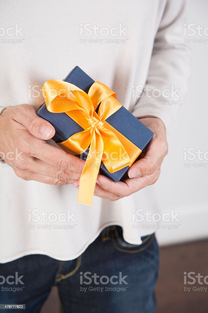 hands holding blue gift stock photo
