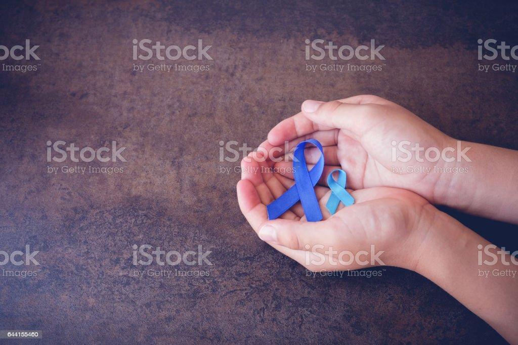 hands holding blue ribbons, toning background stock photo