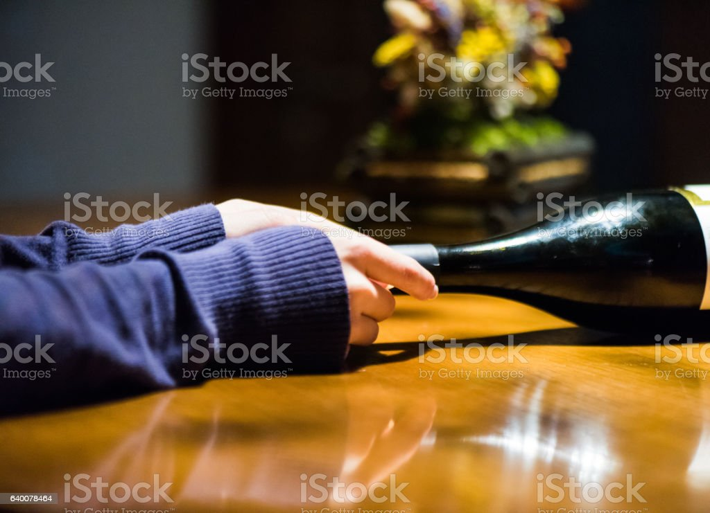 Hands holding bottle of red wine stock photo