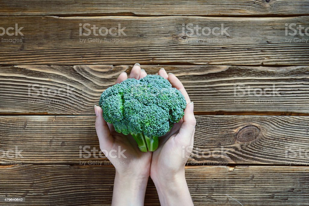 Hands holding broccoli on wooden rustic background stock photo