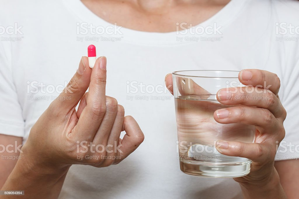 hands holding capsule pill and a glass of water stock photo