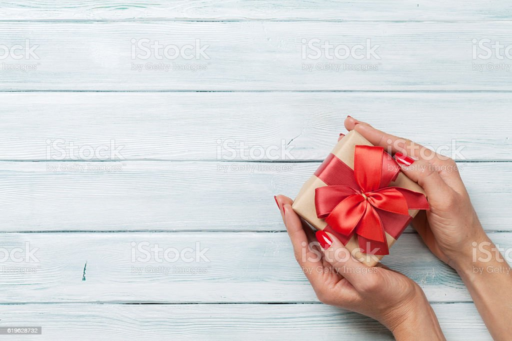 Hands holding christmas or valentines day gift stock photo