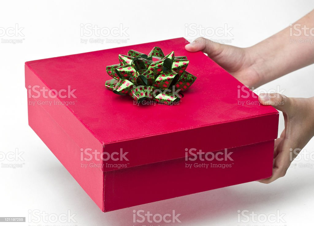 Hands holding Christmas present that is red box with bow. stock photo
