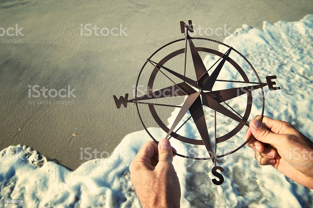 Hands Holding Compass Over Waves Rushing on Beach stock photo