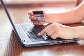 Hands holding credit card and using laptop - online shopping