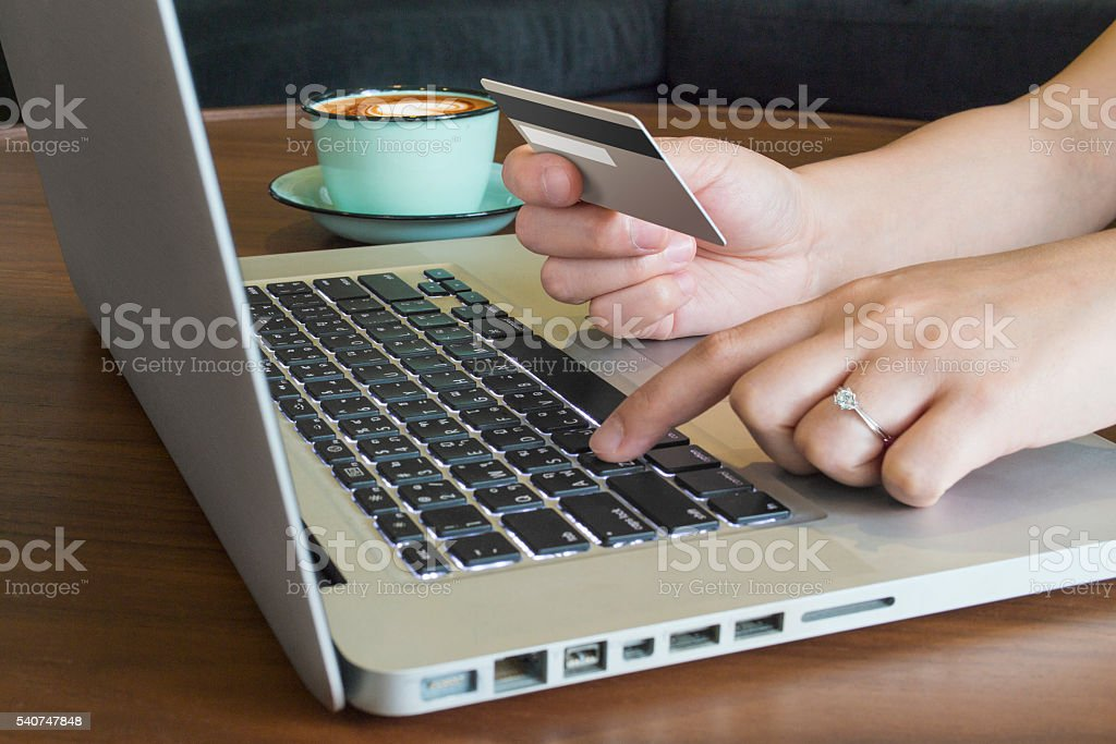 hands holding credit card using laptop for on line shopping stock photo