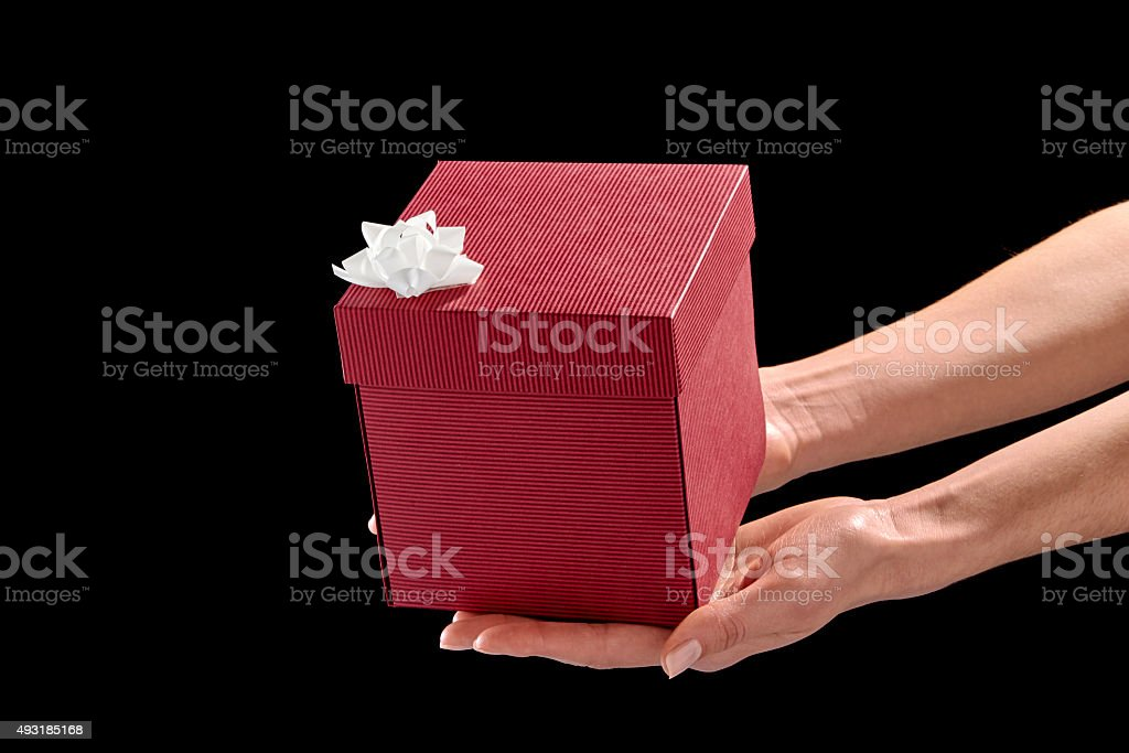 Hands holding cubic red gift box stock photo