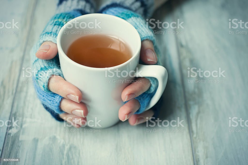 Hands holding cup of hot drink stock photo