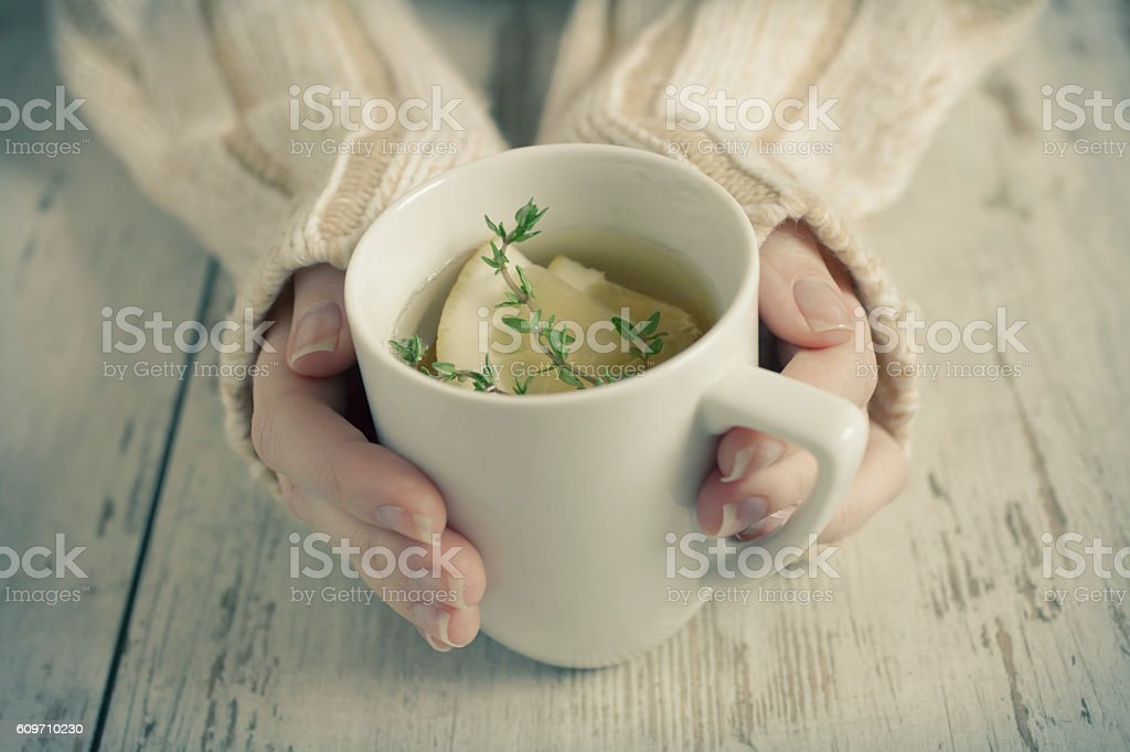 Hands holding cup of tea with lemon stock photo