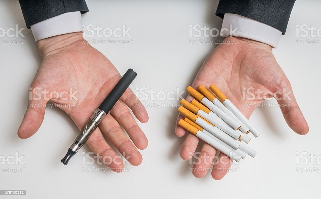 Hands holding electronic and conventional tobacco cigarettes and comparing. stock photo