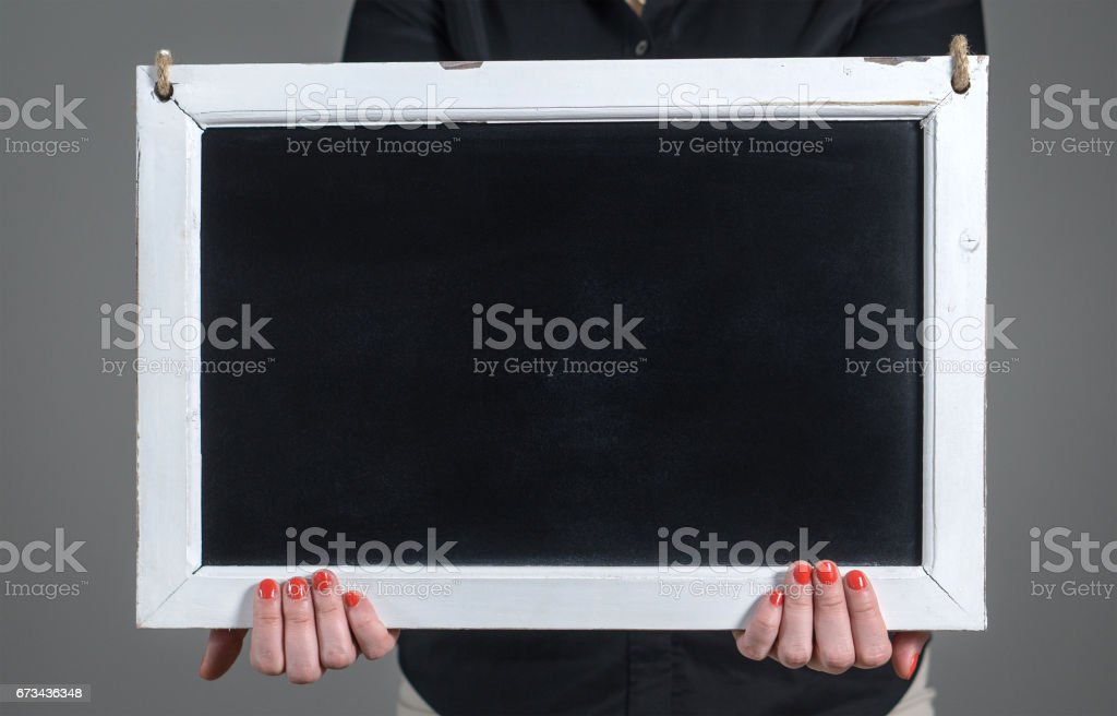 Hands holding empty chalkboard with a lot of free blank copy space for text. Nice template for design, artwork and marketing. stock photo