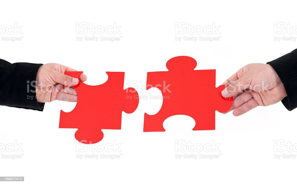 Hands holding fitting puzzle pieces before piecing together royalty-free stock photo