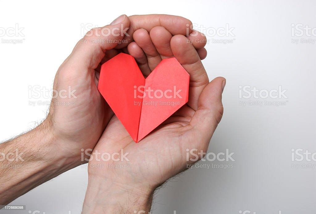 Hands Holding Folded Origami Heart White Background royalty-free stock photo
