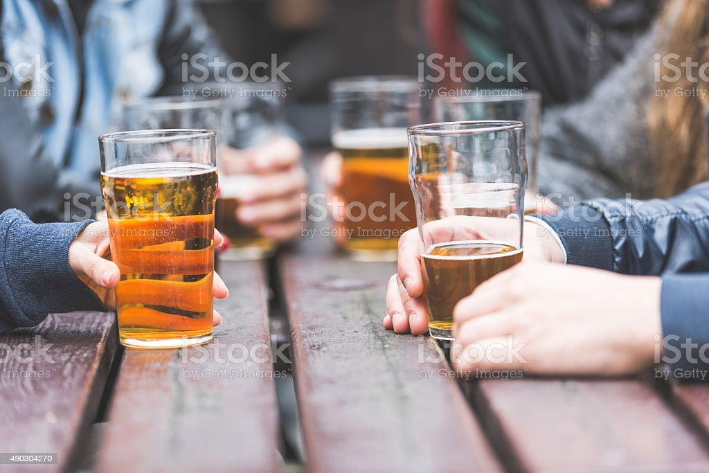 Hands holding glasses with beer on a table in London stock photo
