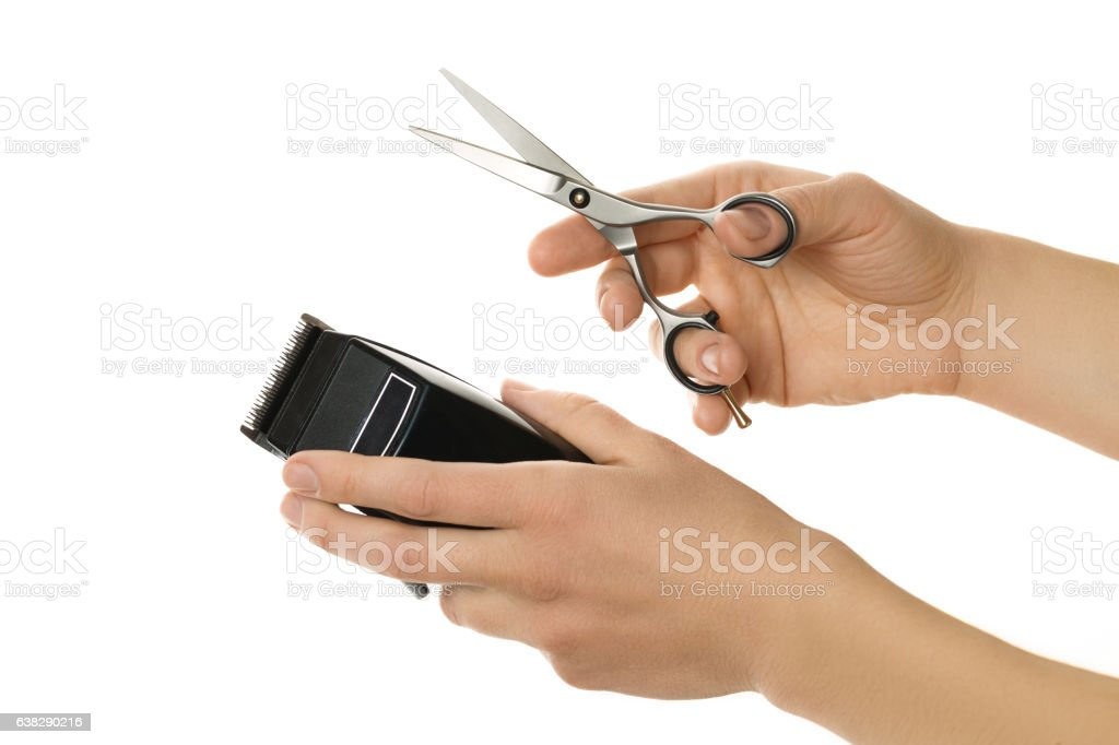 hands holding hair clipper and scissor, isolated on white stock photo