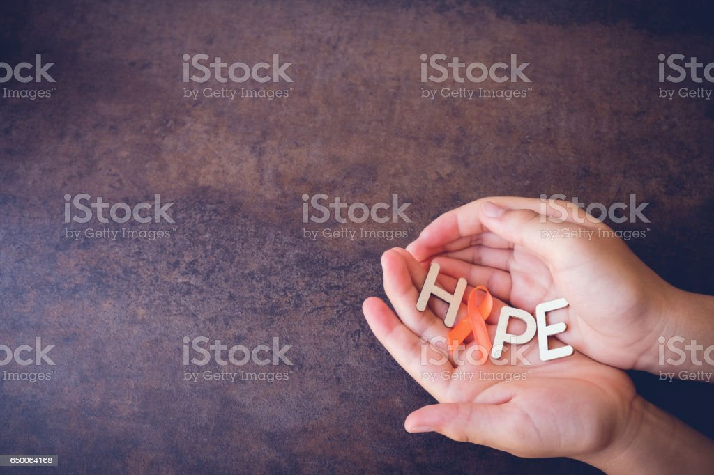 Hands holding HOPE with Orange Ribbons on toning background, Leukemia awareness, Self Injury Awareness Day, Multiple sclerosis awareness, Kidney cancer awareness stock photo