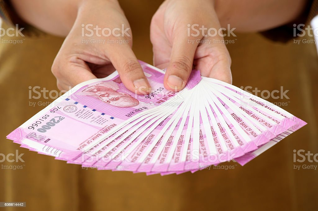 Hands holding Indian 2000 rupee notes stock photo