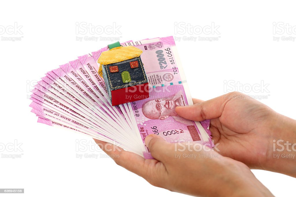 Hands holding Indian currency with house shape stock photo