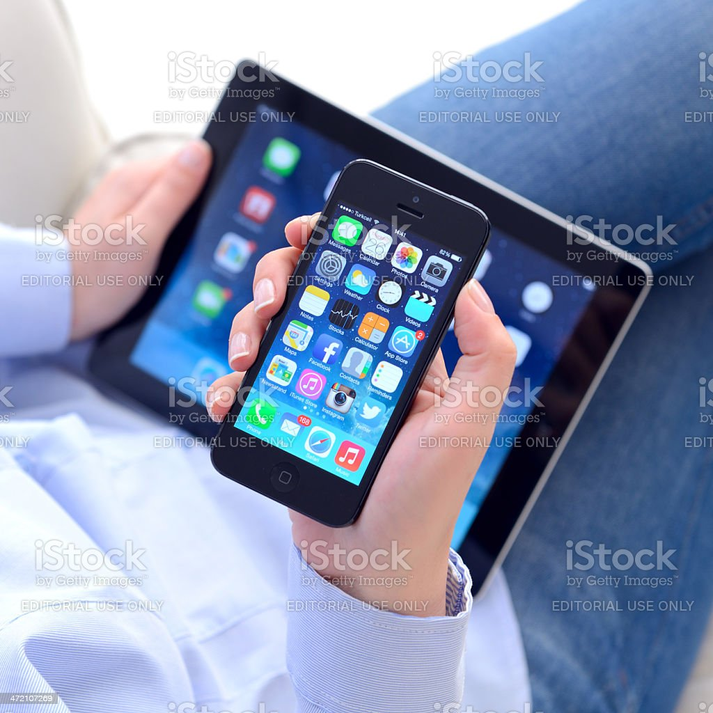 Hands holding iPhone 5 & Apple iPad displaying iOS 7 screen stock photo