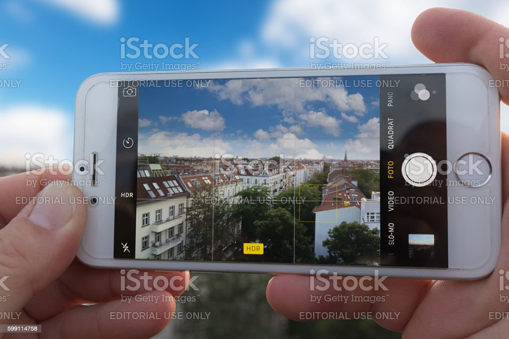 Hands holding Iphone 6, taking picture of city skyline stock photo