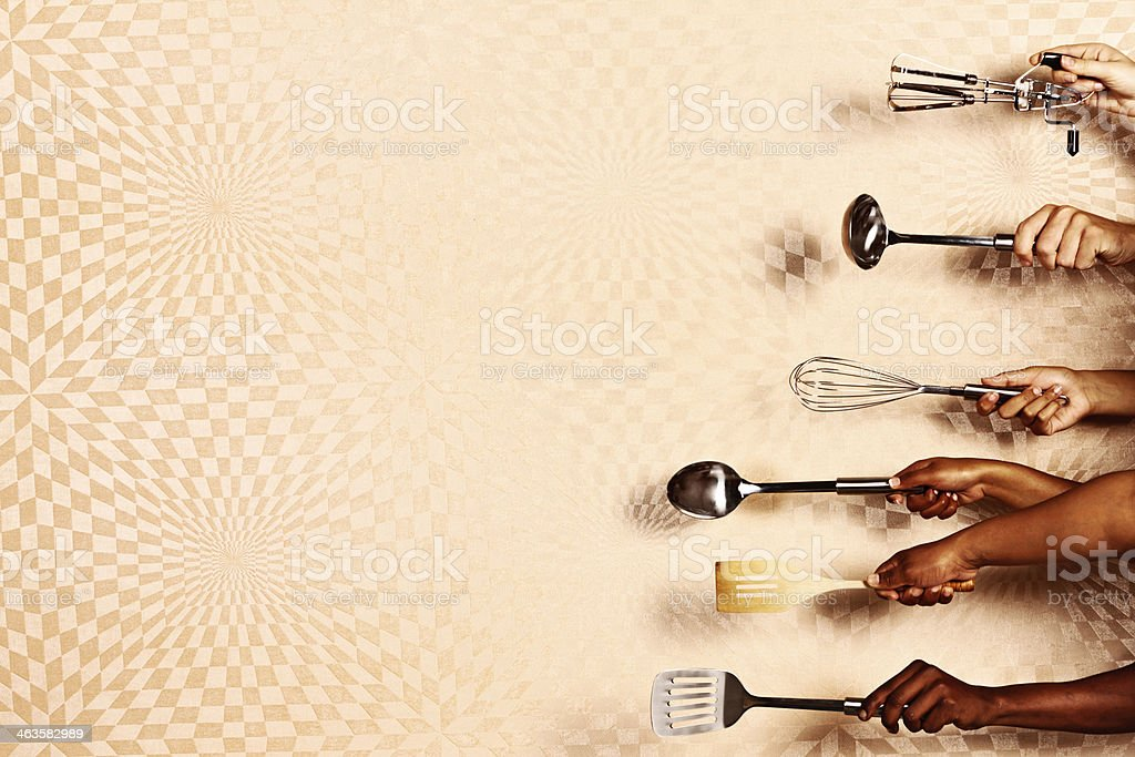 Hands holding kitchen utensils pointing to left against psychedelic background stock photo