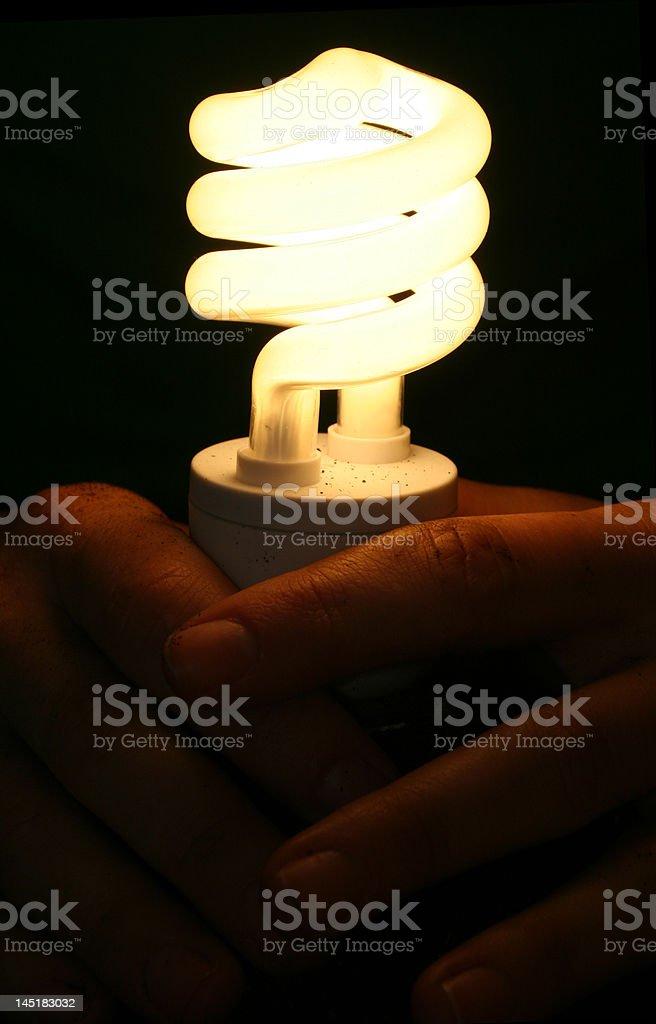 Hands holding lightbulb stock photo