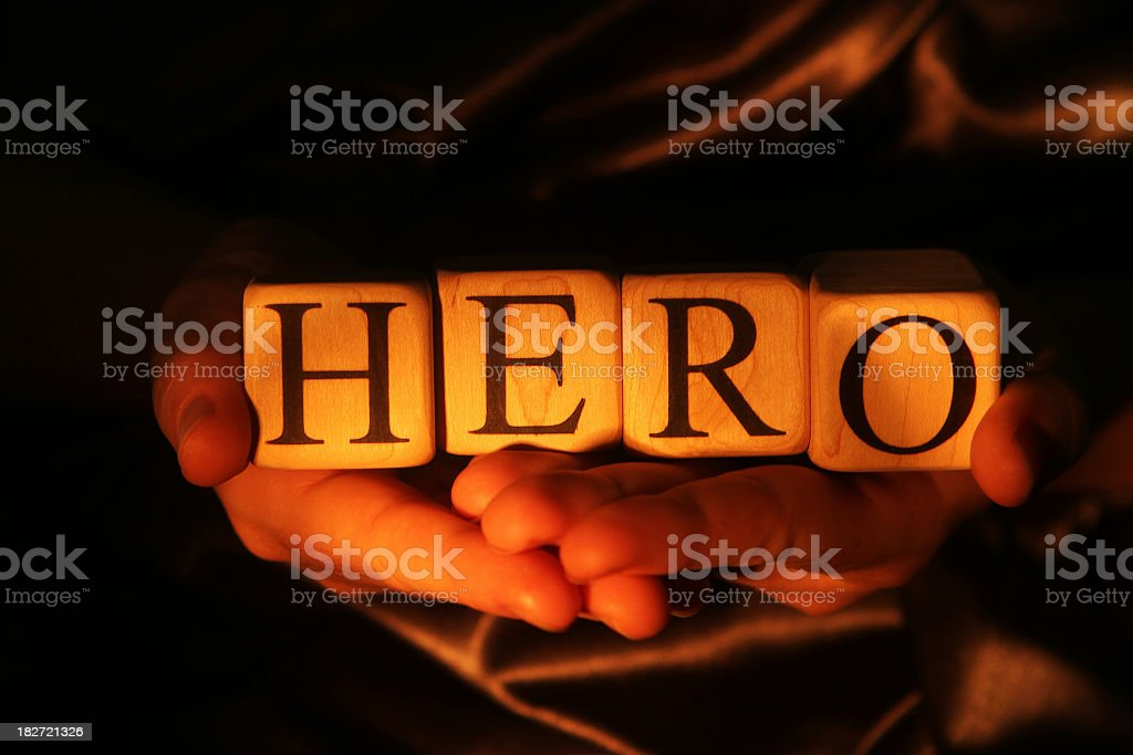 Hands holding lighted blocks spelling hero royalty-free stock photo