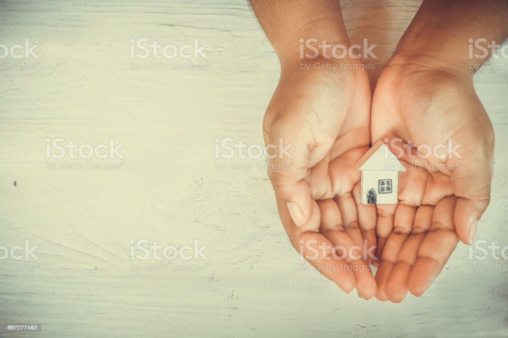 Hands holding little wooden house  model stock photo