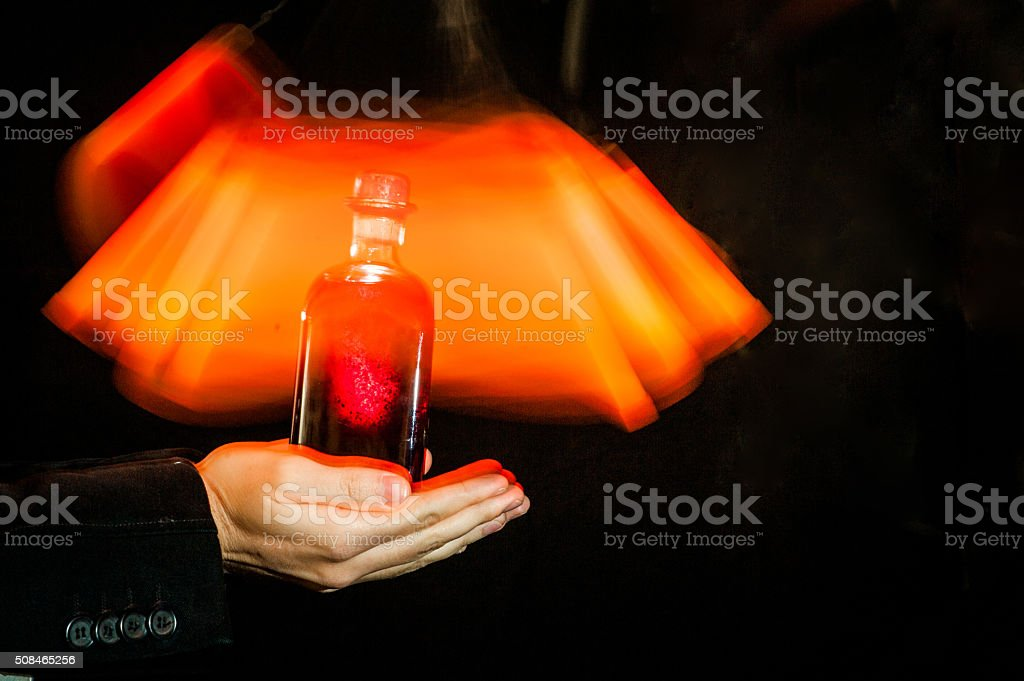 Hands Holding Love Potion in the Bottle, Light Painting stock photo