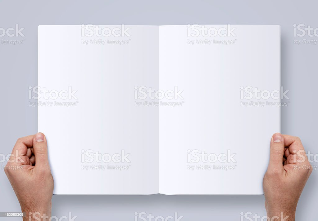 Hands Holding Magazine With Two Clipping Paths stock photo